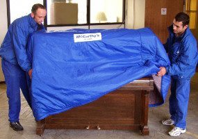 Two removals men packing a piano